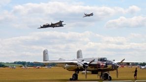 B17 & Mustang flying over the parked Mitchell Bomber