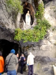 A helping hand to collect Lourdes water from the rock