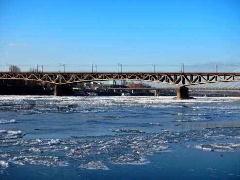 The Vistula river, reflecting the blue, blue sky, is beginning to ice over