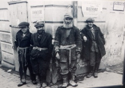 Jewish carriers standing on a street corner. The announcement proclaiming establishment of the ghetto on the wall behind them - from a sign board in the museum at Majdanek