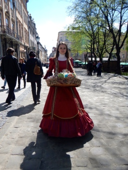 A beautiful young lady selling souvenirs dressed in clothes of old