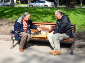There were many men on bench seats playing chess in ernest