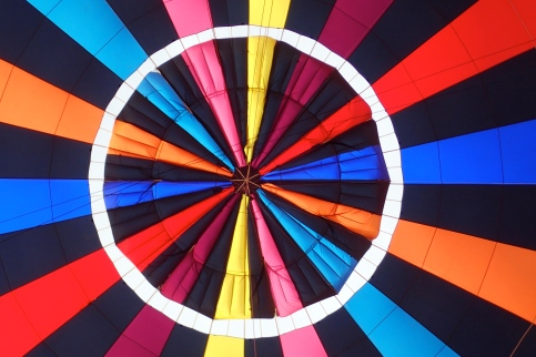 Looking up into the brightly coloured hot air balloon canopy