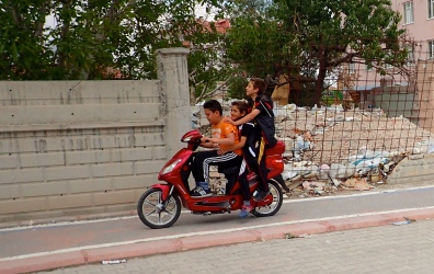 Three up .. and loving it. This is not uncommon in Turkey, and wearing safety gear is unusual