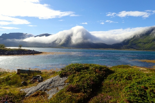 Magical clouds near Lodingen spilling over the mountains into the sea in Norway